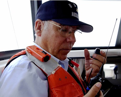 VHF radios are standard equipment aboard all marine vessels. Here, USCG Auxiliarist Bob Sterzenbach uses a VHF marine radio to contact Radio Newport during a safety patrol off Southern California. Photo credit: USCG Auxiliary.